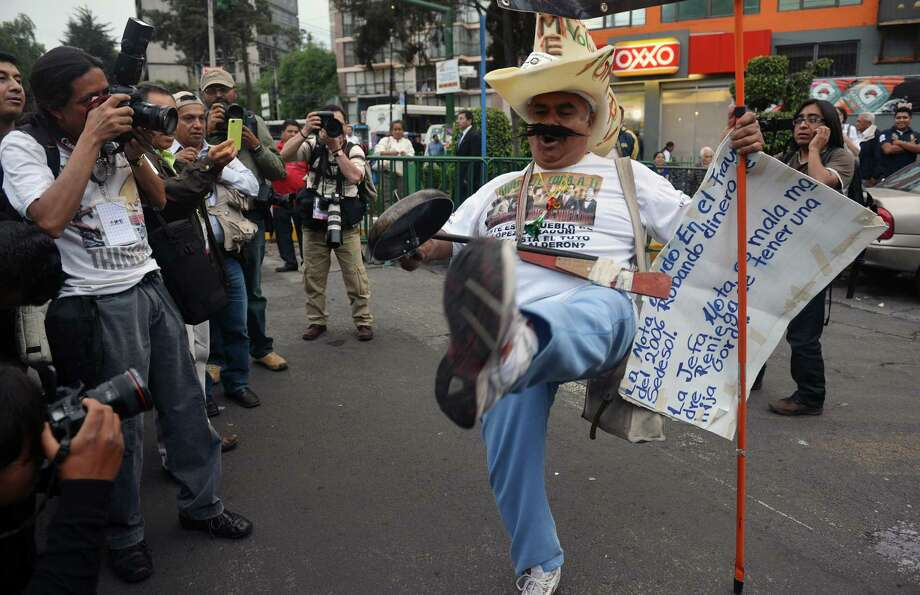 A supporter of the presidential candidate for the leftist coalition Progressive Movement of Mexico, Andres Manuel Lopez Obrador, dances outside the World Trade Center building, during the fist debate of presidential candidates on May 6, 2012 in Mexico City.   AFP PHOTO/ Yuri CORTEZ        (Photo credit should read YURI CORTEZ/AFP/GettyImages) Photo: YURI CORTEZ, Getty Images / 2012 AFP