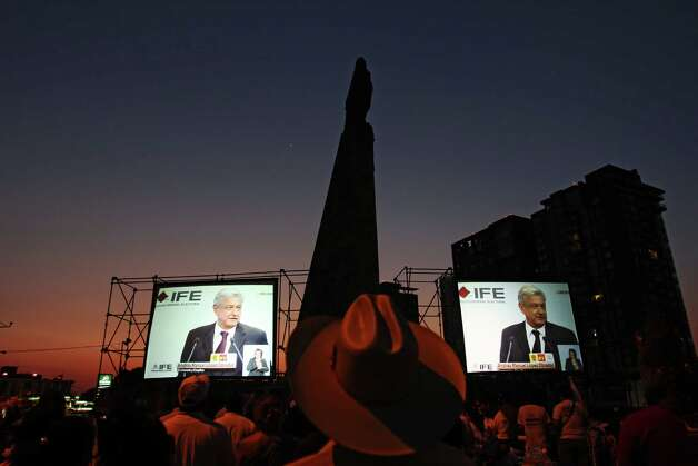 People watch the debate of presidential candidates on giant screens on a street of Guadalajara, Mexico on May 6, 2012. Four presidential candidates are taking part of the first debate promoted by the Federal Electoral Institute. AFP PHOTO/Hector Guerrero        (Photo credit should read HECTOR GUERRERO/AFP/GettyImages) Photo: HECTOR GUERRERO, Getty Images / 2012 AFP