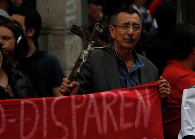 A man holds a cross while protesting the recent slaying of journalists outside of the site where the