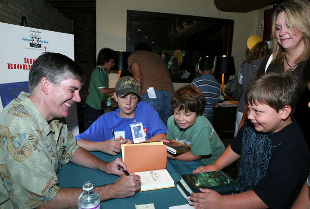 Author Rick Riordan signs his books for fans. Photo: LELAND A. OUTZ, For The Express-News / SAN ANTONIO EXPRESS-NEWS