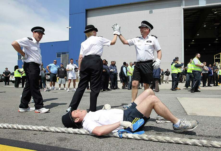 "Olly Chapman of the Metropolitan Police Services in London catches his breath after his team pulled a Jet Blue A320 plane 100 feet during the third annual Jet Blue Airbus A320 Plane Tug at JFK Airport on May 7, 2012 in New York City. Members of the London's Metropolitan Police Services went head-to-head with local law enforcement and airport crewmembers to see which team of up to 16 people could pull a 150,000 pound Jet Blue A320 aircraft 100 feet in the fastest time. A team of TSA employees had the fastest time of 32 seconds. The ""Brits VS Yanks"" competition raises money and awareness for the Joining Against Cancer Kids (JACK) Foundation, a UK based organization that rase money for Neuroblastoma cancer research. Photo: Justin Sullivan, Getty Images / 2012 Getty Images"