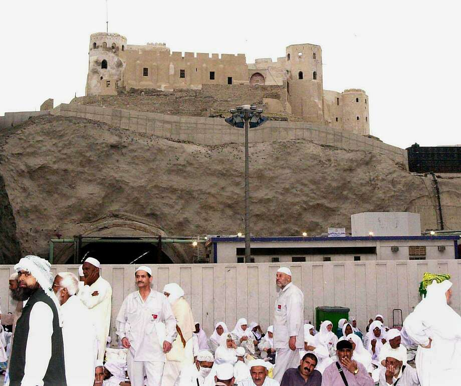 Muslim pilgrims sit under an Ottoman fortress overlooking the Grand Mosque in Mecca, Saudi Arabia, in March 2001. Saudi authorities subsequently demolished the fortress to make way for a $533 million housing project. Photo: MAHMOUD MAHMOUD, AFP/Getty Images / AFP