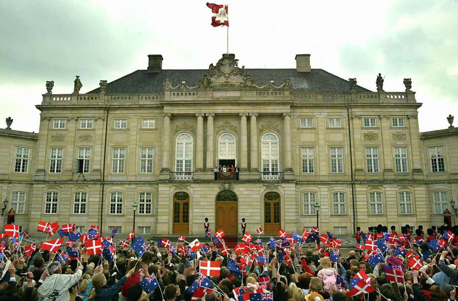 Thousands of well wishers wave flags at Crown prince Frederik and Crown princess Mary of Denmark, standing on  the  balcony at  Amalienborg castle  in Copenhagen, on May 14, 2004, after their wedding. Photo: ODD ANDERSEN, AFP/Getty Images / 2004 AFP