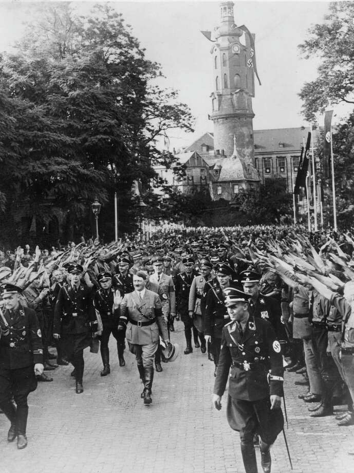 German chancellor Adolf Hitler acknowledges the cheers and salutes of the crowd at Weimar on July 4, 1936, during the 10th anniversary celebrations of the first Nazi Party congress.  Weimar Castle is in the background. Photo: Keystone, Getty Images / Hulton Archive