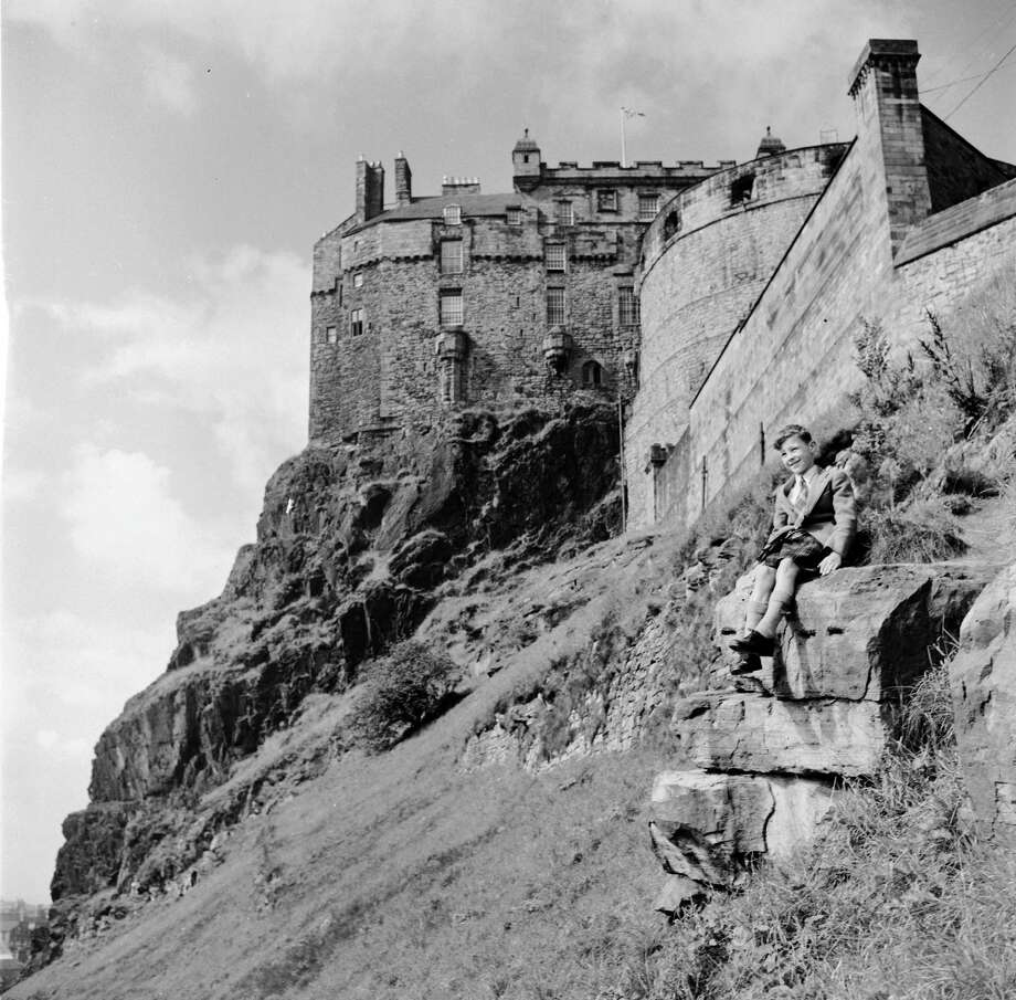 A boy wearing a kilt sits on a rock near Edinburgh Castle, in Edinburgh, Scotland, circa 1950. The oldest part of the building is St Margaret's Chapel, dating from circa 1100 and named after King Malcolm III's wife. The chapel only survived Robert the Bruce's attack in 1313 because he ordered his men to leave it untouched. Edinburgh Castle became a royal residence when James I was murdered in Perth in 1437, and his widow, Joan Beaufort, moved the Royal Court and her son, James II, to Edinburgh. The Scottish crown jewels, the Honours of Scotland, were put on display there after Sir Walter Scott discovered where they had been hidden during the time of Oliver Cromwell. Photo: George Pickow, Getty Images / Hulton Archive