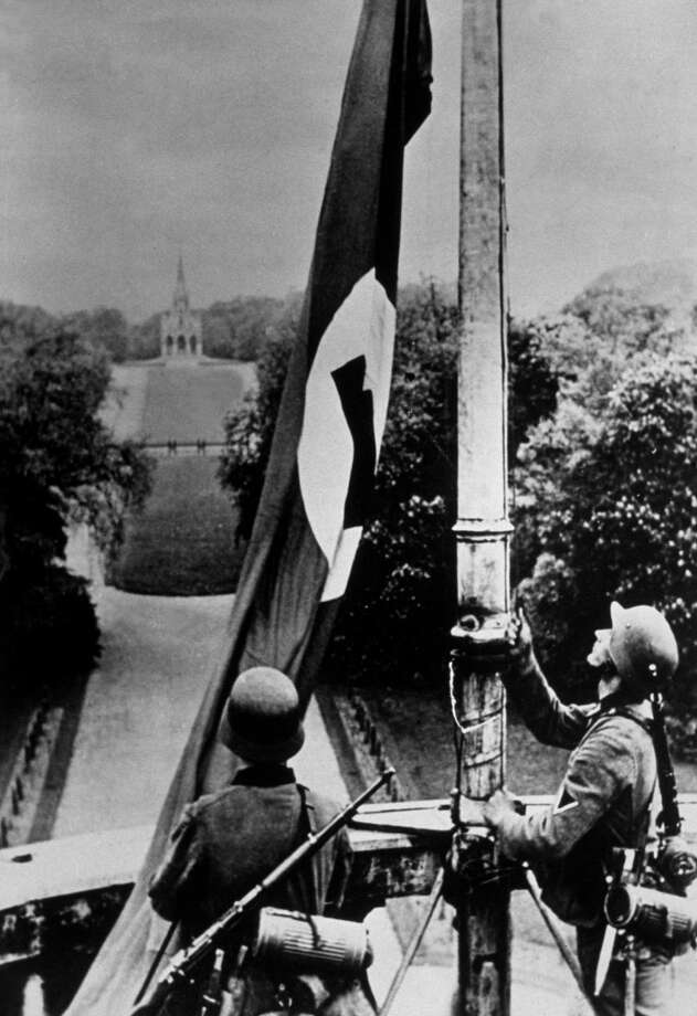 German troops hoist the Nazi flag on the Royal Castle at Laeken, near Brussels, Belgium after their invasion in 1940. Photo: Keystone, Getty Images / Hulton Archive