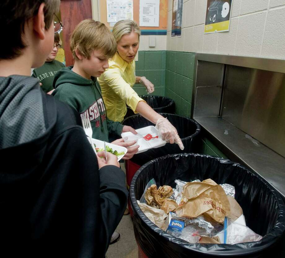 Kellie Ackerman, a local mother and volunteer, guides students to the proper recycling container during lunch at Scotts Ridge Middle School's cafeteria in Ridgefield Tuesday, April 24, 2012 Photo: Scott Mullin