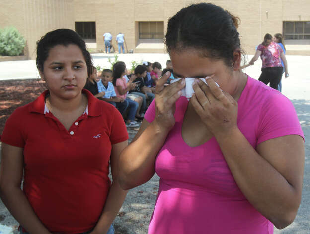 Jennifer Ruiz, 25, (right) pauses before going into Brackenridge Elementary School Monday, May 7, 2012. Two of Ruiz's children died Sunday, May 6, 2012, when the sport utility vehicle they were traveling in blew a tire and rolled on Interstate 35 near Loop 410. Jesse Panchame, 4, died at the scene of the crash and Keylin Panchame, 6, died at University Hospital. The driver of the SUV, Benjamin Vallegos, 26, fled from the scene on foot. Police are still searching for Vallegos. On the left is Ruiz's niece, Natalie Lopez. Lopez was not in the accident. Photo: John Davenport, San Antonio Express-News