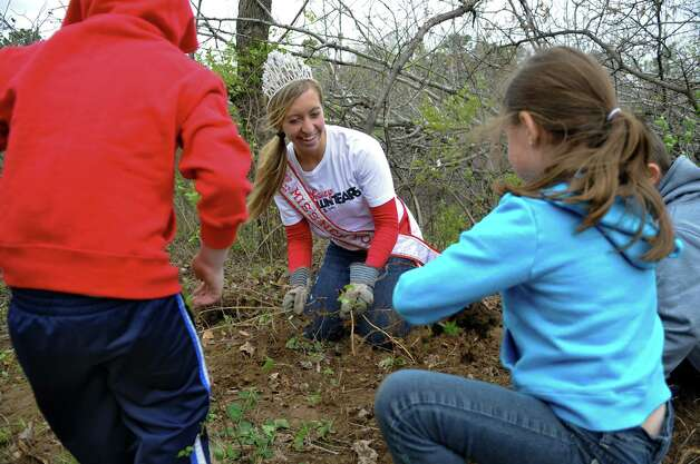 America's Miss New York Kelly Slingerland, center, pulls roots and weeds while volunteering her time at the Albany Pine Bush Discovery Center along with Noah Bocketti, 6, left, his brother Jordan, 8, far right, and their step sister Emily Fredericks, 8, second from right, of Schenectady, on Sunday April 22, 2012 in Albany, NY. (Philip Kamrass / Times Union ) Photo: Philip Kamrass / 00017359A