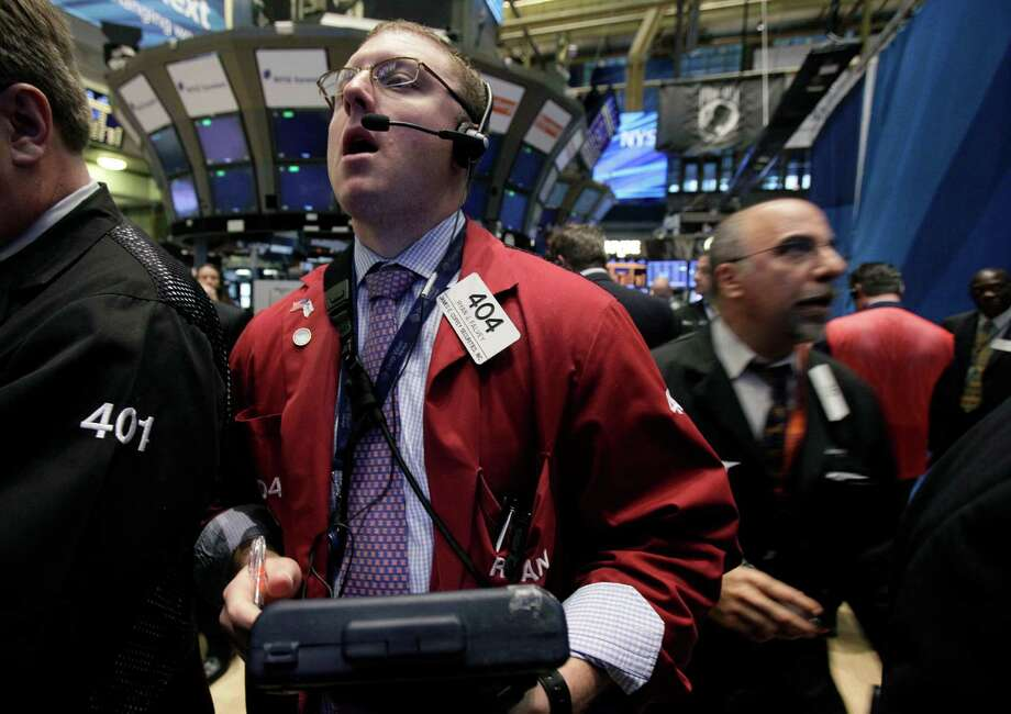In a May 3, 2012, photo, trader Ryan Falvey, left, works on the floor of the New York Stock Exchange.  Wall Street is poised to open lower with Dow futures and the S&P 500 futures both 0.7 percent lower.   (AP Photo/Richard Drew) Photo: Richard Drew