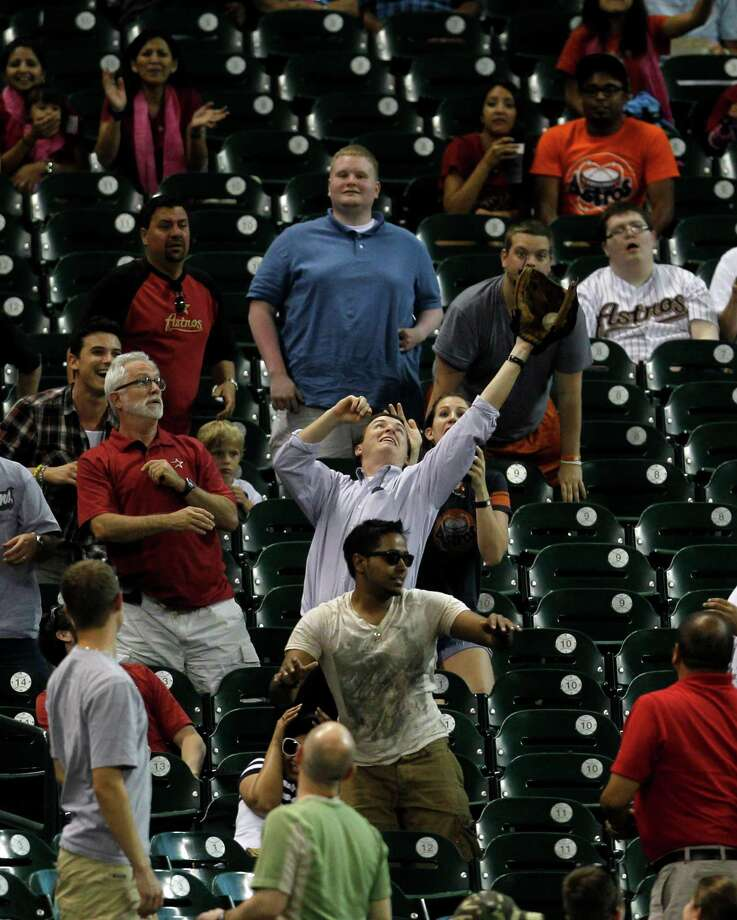 A fan catches a foul ball during the 2nd inning of an MLB baseball game at Minute Maid Park on Monday, May 7, 2012, in Houston. Photo: Karen Warren, Houston Chronicle / © 2012  Houston Chronicle