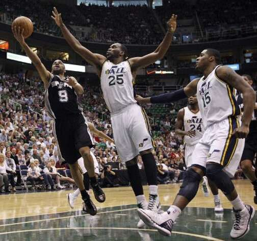 The Spurs' Tony Parker drives to the basket around the Jazz's Al Jefferson and Derrick Favors during first half action of Game 4 of the Western Conference first round Monday May 7, 2012 at EnergySolutions Arena in Salt Lake City, Utah. EDWARD A. ORNELAS/SAN ANTONIO EXPRESS-NEWS (EDWARD A. ORNELAS / SAN ANTONIO EXPRESS-NEWS)