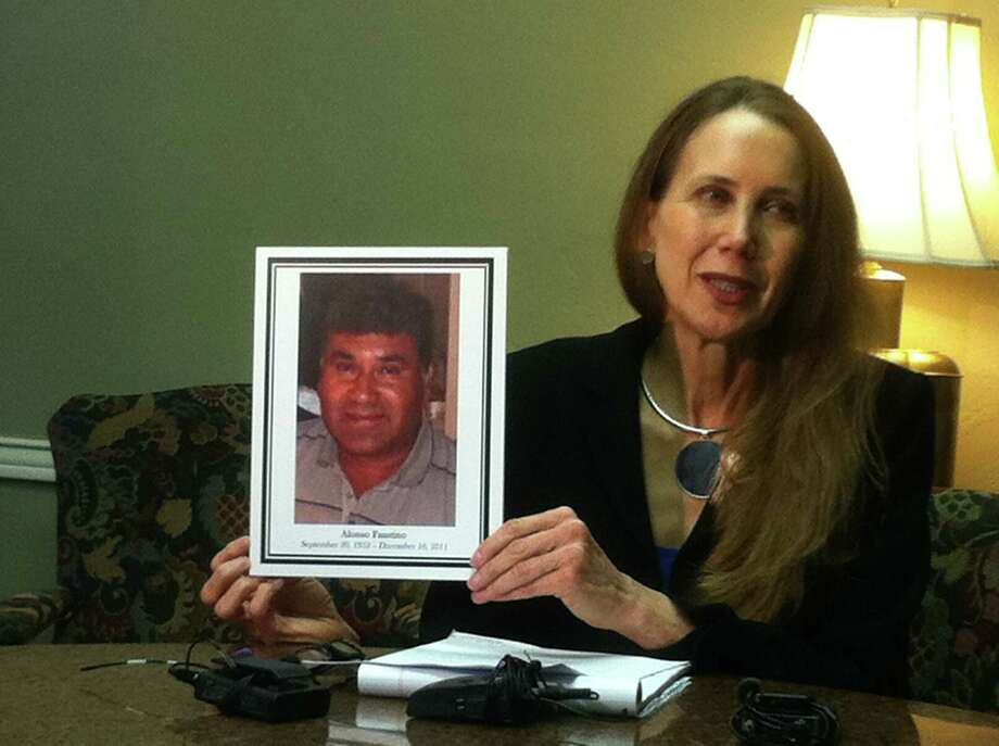 Civil attorney Marynell Maloney shows a photo of slain carwash customer Faustino Alonso Monday during a press conference to announce a wrongful death lawsuit against the East Side business where he was shot. Photo: Craig Kapitan, San Antonio Express-News