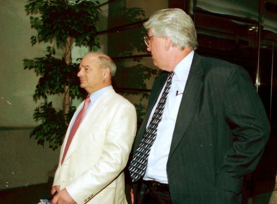 In this May 20, 1998 photo, Nelson Hallahan, right, turns his head from the camera as he leaves the Becker Building in Peoria, Ill., with his attorney, Gary Rafool, after an appearance in bankruptcy court. On Saturday, May 5, 2012, Hallahan and wife, Janet, were arrested by U.S. marshals in Tonopah, Ariz., after being on the lam a dozen years after they fled punishment for running a Ponzi scheme that targeted friends, the elderly, and even family members, authorities said. (AP Photo/Journal Star, Larry Brooks) Photo: Larry Brooks, Associated Press