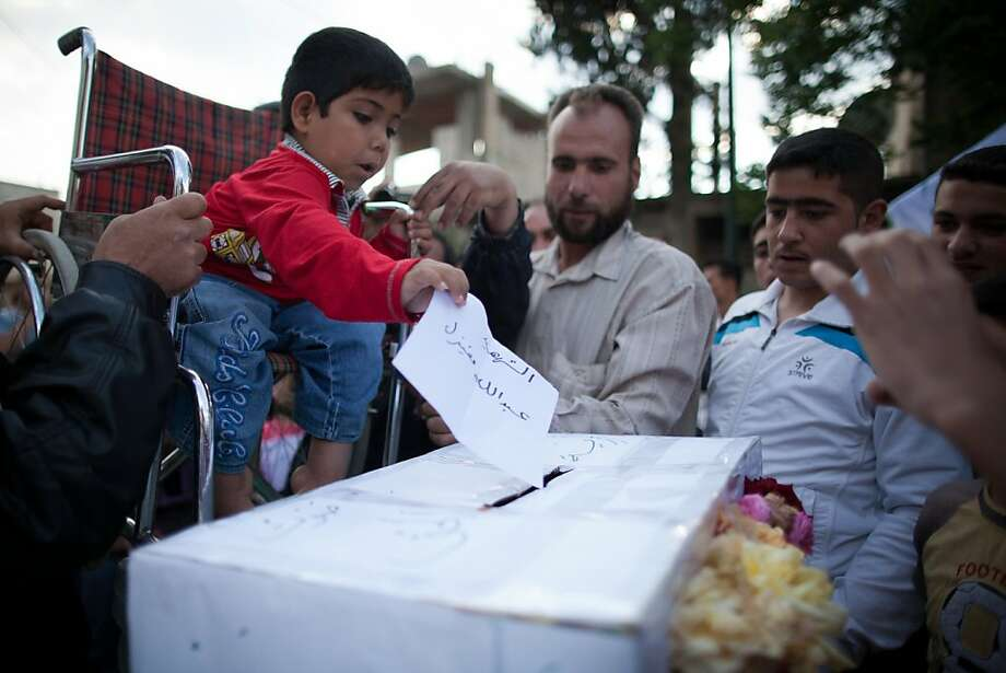 "A handicapped Syrian boy casts a paper bearing the name of a ""martyr"" in coffin-like symbolic ballot boxes during an anti-elections demonstration in the city Qusayr, 15 kms (nine miles) from Homs in restive central Syria, on May 7, 2012, as polling stations opened across the country for the first ""multiparty"" parliamentary vote in five decades. The Syrian opposition dismissed the elections as a sham and refused to participate. AFP PHOTO/STRSTR/AFP/GettyImages Photo: Str, AFP/Getty Images"