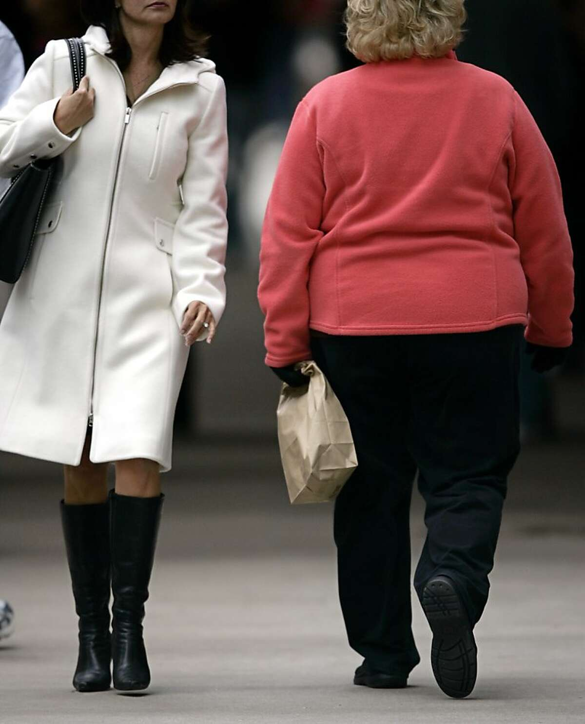 """(FILES)Women walk on Michigan Avenue in this October 19, 2006 photo in Chicago, Illinois. Forty-two percent of the US population could be obese by 2030, up from about one-third currently, and the associated rise in health woes would likely cost $550 billion over two decades, said a study on May 7, 2012. In real numbers, the increase would mean about 32 million more obese people, said the forecast led by researchers at Duke University in North Carolina and published in the American Journal of Preventive Medicine. An adult with a body mass index of 30 or higher is considered obese, such as a person who is 5'9"""" (1.75 meters tall) and weighs over 203 pounds (92 kilograms), according to the US Centers for Disease Control and Prevention. AFP PHOTO/ JEFF HAYNESJEFF HAYNES/AFP/GettyImages"""