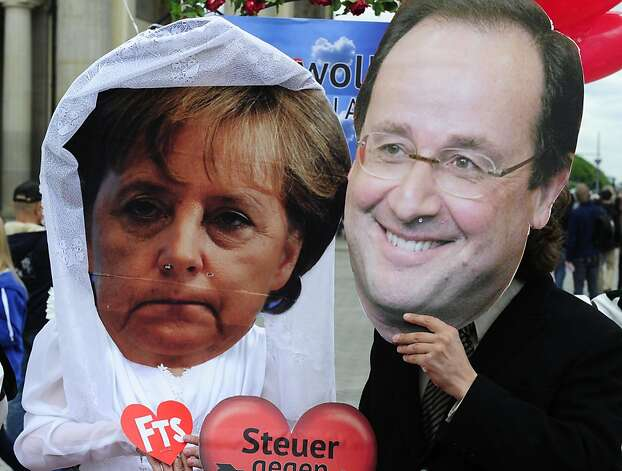 Activists wear masks featuring German chancellor Angela Merkel (L) and incoming French socialist president Francois Hollande (R) as they perform a fake marriage in front of the Brandenburg Gate in Berlin, on May 7, 2012. Non governmental organisations such as Oxfam and Attac organised the action to call for an introduction of a financial transaction tax in Europe one day after the second round of French Presidential election. AFP PHOTO / JOHN MACDOUGALLJOHN MACDOUGALL/AFP/GettyImages Photo: John Macdougall, AFP/Getty Images