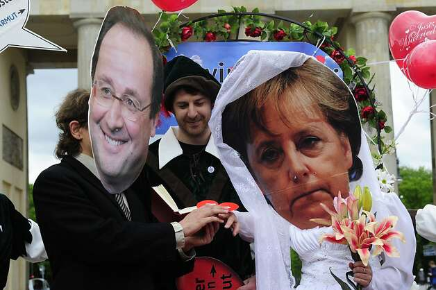 Activists wear masks featuring German chancellor Angela Merkel (R) and incoming French socialist president Francois Hollande (L) as they perform a fake marriage in front of the Brandenburg Gate in Berlin, on May 7, 2012. Non governmental organisations such as Oxfam and Attac organised the action to call for an introduction of a financial transaction tax in Europe one day after the second round of French Presidential election. AFP PHOTO / JOHN MACDOUGALLJOHN MACDOUGALL/AFP/GettyImages Photo: John Macdougall, AFP/Getty Images
