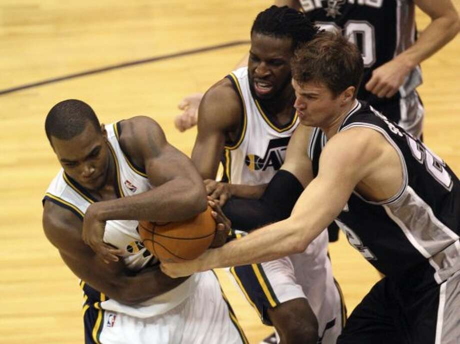 The Spurs'  Tiago Splitter ties up Utah Jazz Paul Millsap for a jumpball during the second half of Game 4 in the Western Conference first round at EnergySolutions Arena in Salt Lake City, Monday, May 7, 2012. The Spurs won 87-81 and swept the series, 4-0. In back is DeMarre Carroll. Jerry Lara/San Antonio Express-News (Jerry Lara / San Antonio Express-News)