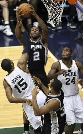 The Spurs'  Kawhi Leonard grabs a rebound from the Jazz's Derrick Favors during the second half of game four in the Western Conference first round at EnergySolutions Arena in Salt Lake City, Monday, May 7, 2012. The Spurs won 87-81 and swept the series, 4-0. Jerry Lara/San Antonio Express-News (Jerry Lara / San Antonio Express-News)