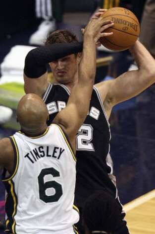 The Spurs'  Tiago Splitter grabs a rebound from Utah Jazz Jamaal Tinsley during the second half of Game 4 in the Western Conference first round at EnergySolutions Arena in Salt Lake City, Monday, May 7, 2012. The Spurs won 87-81 and swept the series, 4-0. Jerry Lara/San Antonio Express-News (Jerry Lara / San Antonio Express-News)
