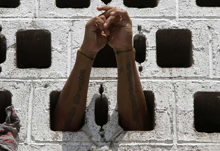 A prisoner rests his arms in the wall of his cell during a Mass for prisoners in the courtyard of La Esperanza penal center in San Salvador, El Salvador, Monday, May 7, 2012. The prisoners asked for Monsignor Fabio Colindres to hold a Mass for them at the prison.  (AP Photo/Luis Romero) Photo: Luis Romero, Associated Press