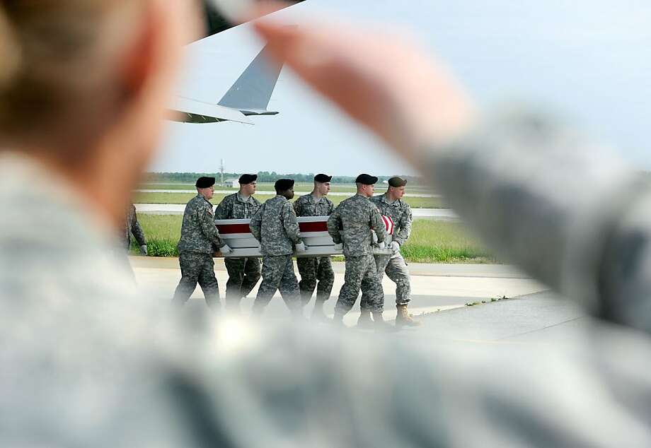 An Army carry team moves a transfer case containing the remains of Capt. Gregory L. Childs on Monday, May 7, 2012 at Dover Air Force Base, Del. According to the Department of Defense, Childs, of Warren, Ark., died in Afghanistan while supporting Operation Enduring Freedom. (AP Photo/Steve Ruark) Photo: Steve Ruark, Associated Press