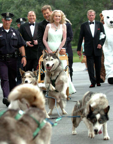 "Socialite Marylou Whitney arrives at her gala ""A Night in Alaska"" on a dog sled with Iditarod musher Martin Buser, center left, on Friday Aug. 3, 2007, at the Canfield Casino in Saratoga Springs, N.Y. At left is Whitney's husband John Hendrickson. (Cindy Schultz/Times Union archive) Photo: CINDY SCHULTZ / ALBANY TIMES UNION"