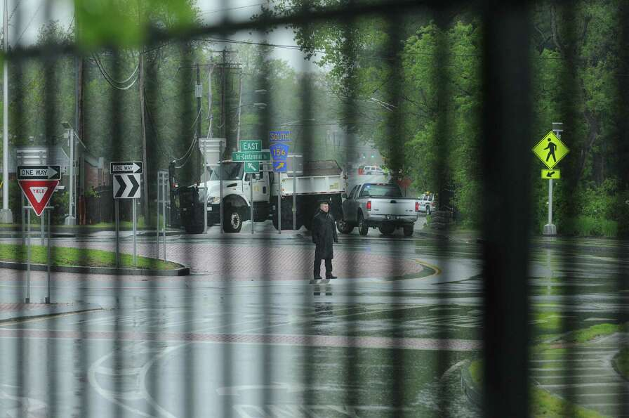 A law enforcement officer stands in the middle of the shut down rotary at Fuller Road and Tricentenn