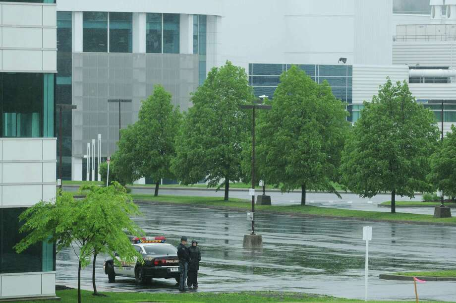 Law enforcement officers stand guard in an empty parking lot at the  College of Nanoscale Science and Engineering on the campus of the University at Albany as they await the arrival of President Obama on Tuesday morning, May 8, 2012 in Albany, NY.  (Paul Buckowski / Times Union) Photo: Paul Buckowski