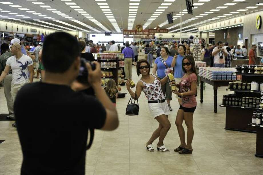 Visitors from the Philippines ? Darrel Malsit (from left, with camera), Divina Beason and Wilma Gilliam ? were among those at Buc-ee?s new store in New Braunfels on its opening day. Photo: Robin Jerstad, For The Express-News / SA