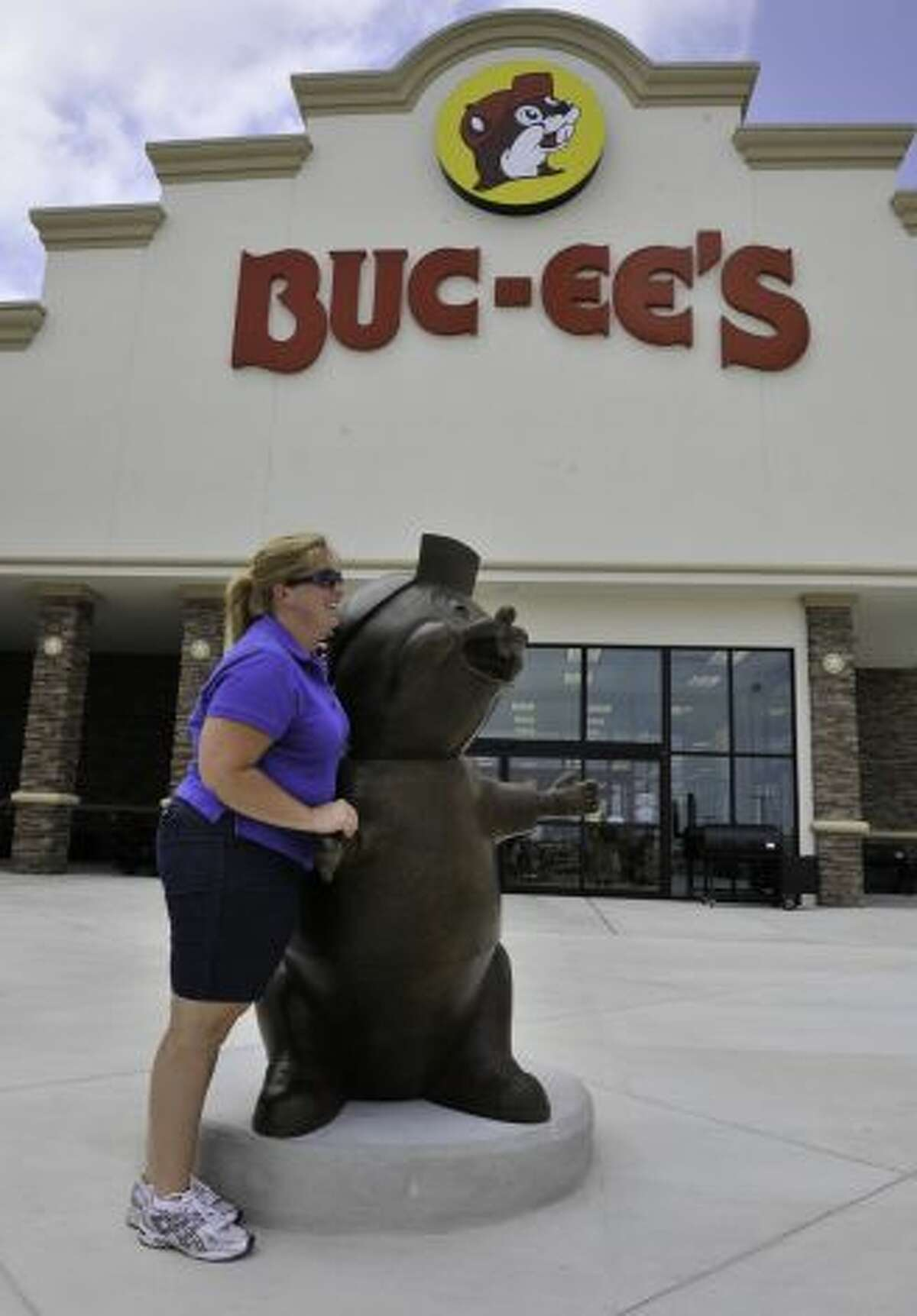 Terri Weaver poses with the Buc-ee statue at the new store, the largest in the chain. General manager Dan Parkinson said new features include wider aisles, a farmers market and an indoor area for hunting equipment. Photo: Robin Jerstad, For The Express-News / SA