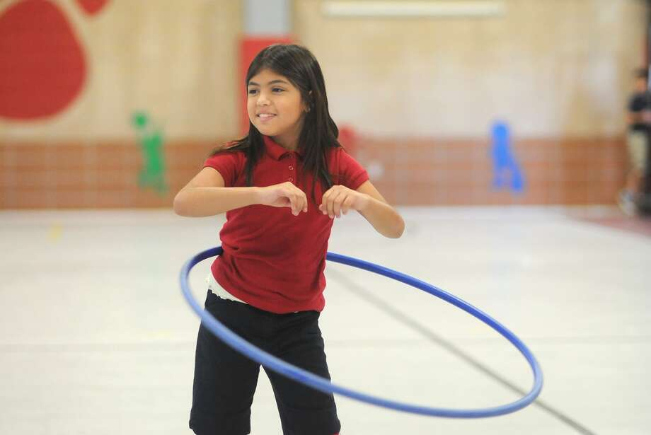 "Nathalia Gomez, 9, a third-grader at Epps Island Elementary exercises with a Hula Hoop as part of the school's ""Be a Champion"" program. Photo: Jerry Baker"