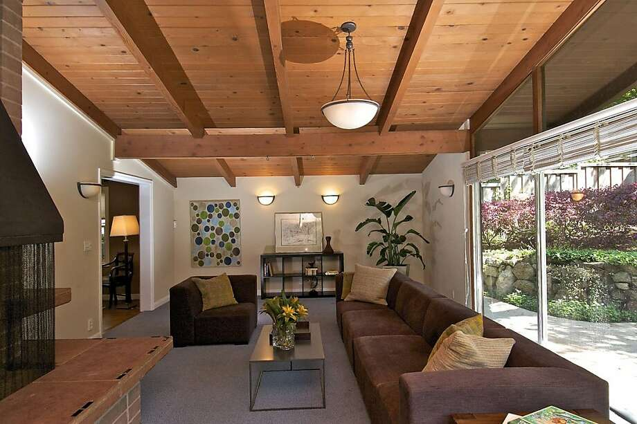 The family room has an exposed beam ceiling and floor-to-ceiling windows overlooking the backyard garden. Photo: George Draper