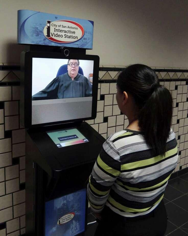 Sylvia Rivera, senior deputy court clerk, demonstrates a video kiosk the city will use for traffic tickets Tuesday, May 8, 2012. Photo: BILLY CALZADA, San Antonio Express-News / SAN ANTONIO EXPRESS-NEWS