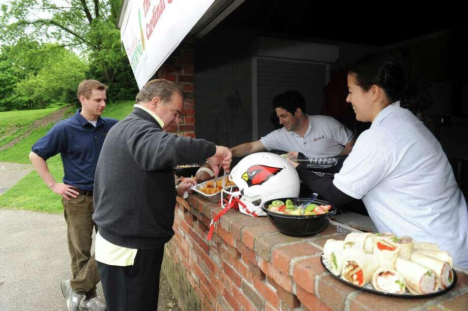 From left: Matt Hurta, managing partner of Garden Catering, and owners Frank Carpenteri Sr., Frank Carpenteri Jr. and Tina Carpenteri taste some of the Greenwich eatery's lunch at the Bird's Nest at Greenwich High School's Cardinal Stadium Tuesday, May 8, 2012. Starting this year, Garden Catering will provide food services for the Greenwich High School football team in exchange for rights to prepare, deliver, market, sell and keep all revenue from food/beverage concessions at the Bird's Nest during the Red-White Game and home games. Photo: Helen Neafsey / Greenwich Time