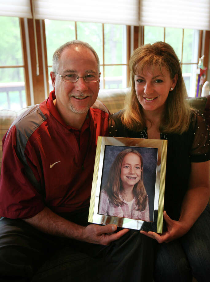 Jeff and Donna Babineau of Stratford hold a photo of their late daughter Erin, who was killed in a car accident when she was 10 years old. Babineau has organised a softball triple header on Saturday, May 12 at DeLuca Field in Stratford to raise money for the Erin Babineau Memorial Fund. The fund supports  youth in the town of Stratford, and recently paid for an indoor turf field at the Sterling House Community Center. Photo: Brian A. Pounds / Connecticut Post