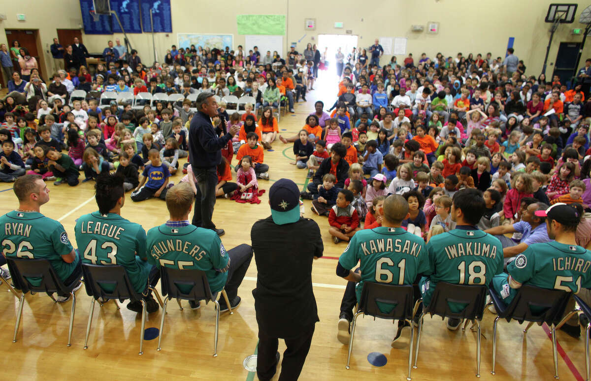 Seattle Mariners players, from left, Brendan Ryan, Brandon League, Michael Saunders, Munenori Kawasaki, Hisashi Iwakuma and Ichiro Suzuki are joined by Rick Rizzs during the annual D.R.E.A.M Team Assembly at TOPS at Seward School in Seattle.