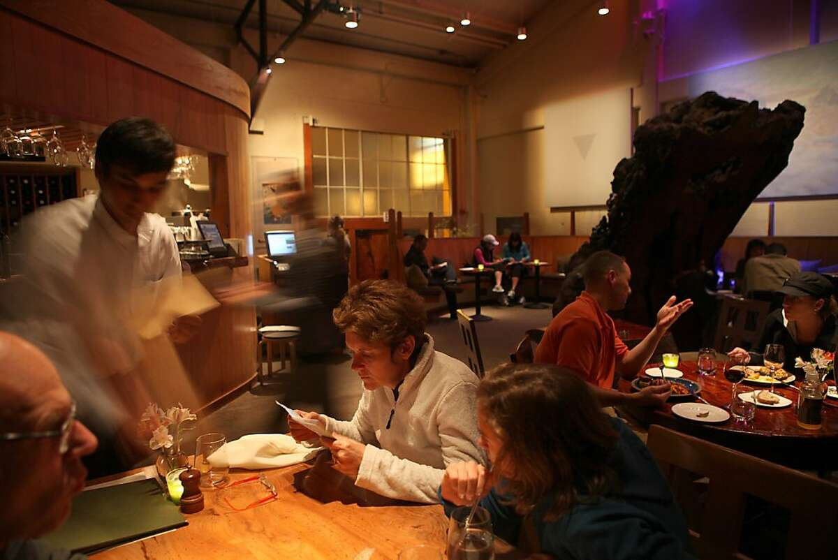 Manager Marty McHalsky (left) handing out menus at Green's Restaurant in Fort Mason in San Francisco, Calif., on Monday, August 22, 2011.