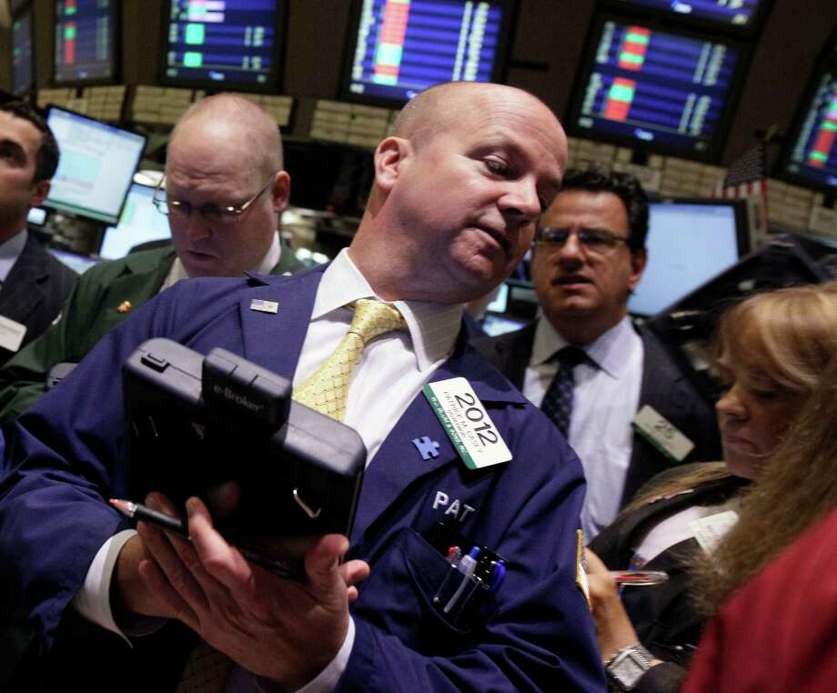 In a Monday, May 7, 2012, photo, trader Patrick Casey, center, works on the floor of the New York Stock Exchange.   Futures pointed to losses on Wall Street with Dow Jones industrial futures  and S&P 500 futures down 0.5 percent.   (AP Photo/Richard Drew) Photo: Richard Drew