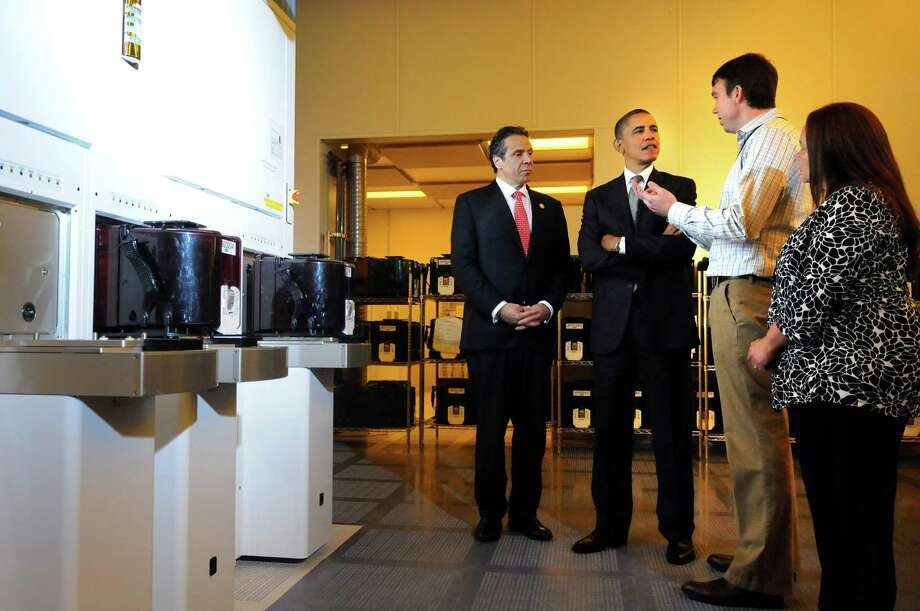 President Barack Obama, center, and Gov. Andrew Cuomo, left,  talk with Martin Rodgers, third from left, CNSE process integration engineer and Maribel Santos-Quinn, CNSE work station operator during a tour of a clean room on Tuesday, May 8, 2012, at University at Albany College of Nanoscale Science and Engineering in Albany, N.Y. (Cindy Schultz / Times Union) Photo: Cindy Schultz / 00017555B
