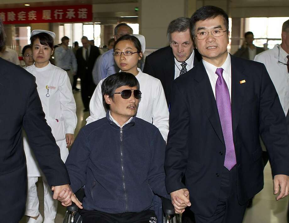 FILE - In this file photo taken Wednesday, May 2, 2012. and released by the U.S. Embassy Beijing Press Office, blind lawyer Chen Guangcheng, center, holds hands with U.S. Ambassador to China, Gary Locke, at a hospital in Beijing. Locke wasn't considered much of a heavyweight on human rights when he became the first Chinese-American ambassador to Beijing last year. Yet, nine months on, Locke's key role in the recent drama over Chen has put him on the front lines of U.S. concerns about China's embattled dissident community. (AP Photo/U.S. Embassy Beijing Press Office, File) Photo: Associated Press