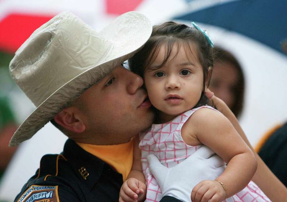 Houston County Sheriff's Honor Guard's A. Benitez, kisses his daughter, Adrianna Benitez, 17 months, before the Harris County Peace Officer's Memorial Ceremony in Houston. The event honored law enforcement officers who have died in the line of duty. Photo: Cody Duty, Houston Chronicle / © 2011 Houston Chronicle