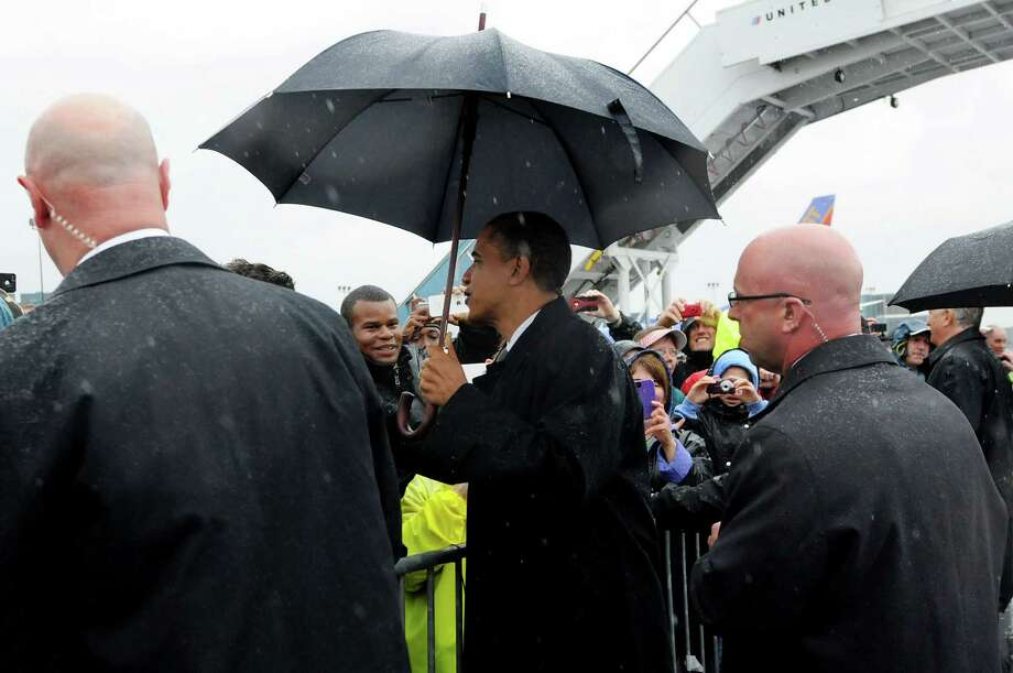 President Barack Obama greets people waiting in the driving rain to see him when he arrives on Tuesday, May 8, 2012, at Albany International Airport in Colonie, N.Y. (Cindy Schultz / Times Union) Photo: Cindy Schultz / 00017555B