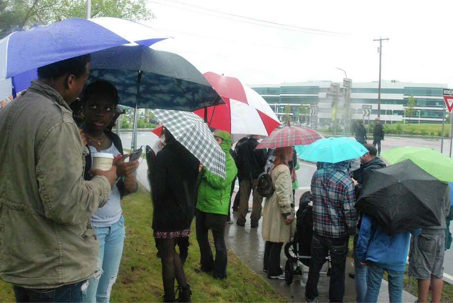 A group of about 70 people wait at the rotary outside the main entrance of the College of Nanoscale Science and Engineering of the University at Albany for President Barack Obama's arrival on Tuesday, May 8, 2012. To the left, freshmen Corey Parker (holding the drink) and Anu Akinwunmi, wait for a glimpse of the president.  (Yi-Ke Peng / Times Union)