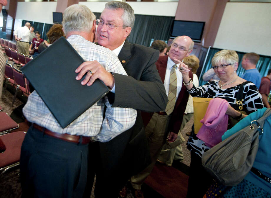 An A&M supporter bids Bill Byrne, right, farewell as his nine-plus-year stint as athletic director comes to an end. Photo: Stuart Villanueva / BRYAN COLLEGE STATION EAGLE
