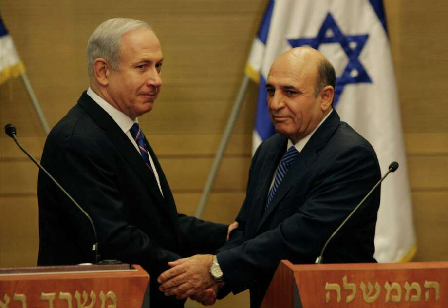 "Israel's Prime Minister Benjamin Netanyahu, left, and Kadima party leader Shaul Mofaz shake hands before holding a joint press conference announcing the new coalition government, in Jerusalem, Tuesday, May 8, 2012. Netanyahu said Tuesday his new coalition government will promote a ""responsible"" peace process with the Palestinians. (AP Photo/Sebastian Scheiner) Photo: Sebastian Scheiner / AP"