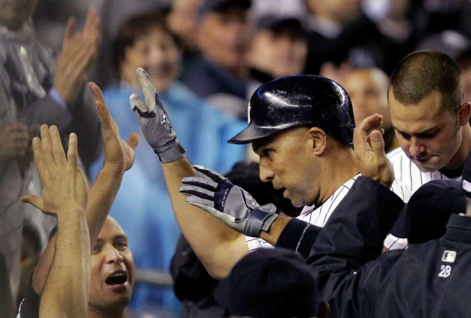 New York Yankees Russell Martin, lower left, greets Raul Ibanez who hit a seventh-inning solo home run, his second of the game, during the Yankees baseball game against the Tampa Bay Rays at Yankee Stadium in New York, Tuesday, May 8, 2012.  (AP Photo/Kathy Willens) Photo: Kathy Willens