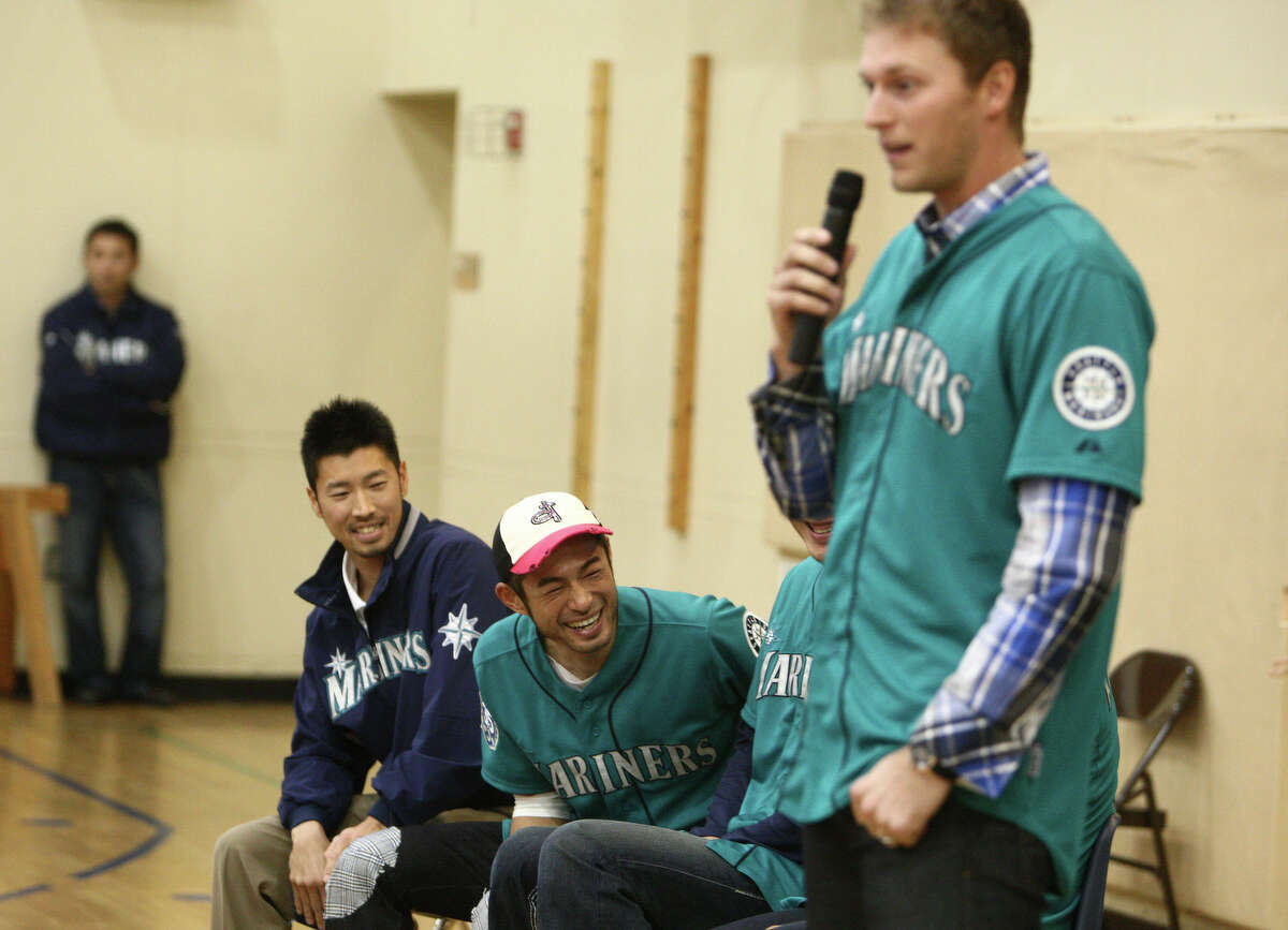 Seattle Mariners player Michael Saunders speaks to students as teammate Ichiro Suzuki jokes in the background during the annual D.R.E.A.M Team Assembly at TOPS at Seward School in Seattle.