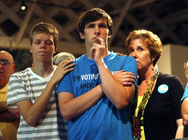 Seth Keel, center, is consoled by his boyfriend, Ian Chambers, left, and his mother Jill Hinton, during a concession speech at an Amendment One opposition party Tuesday, May 8, 2012, at The Stockroom at 230 in downtown Raleigh, N.C. North Carolina voters approved the constitutional amendment Tuesday defining marriage solely as a union between a man and a woman, becoming the latest state to effectively slam the door shut on same-sex marriages. (AP Photo/The News & Observer, Travis Long) MANDATORY CREDIT Photo: Travis Long, Associated Press